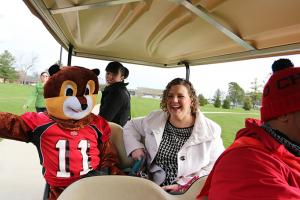 Nino Parker, Andrea Conner, Adrienne Squier, and Scarlet the Squirrel tour campus in a golf cart