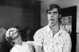 Man in floral print shirt stick out his tounge while woman in white injects something with a needle
