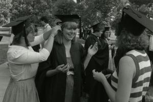 Black and white photo of students adjusting a woman's cap before commencement