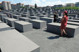 Rectangular grey columns in paved monument with visitors