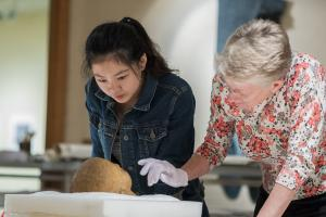 Monessa Cummins, associate professor of classics, and Jiayun Chen '19, a classics and art history double major, examine a marble Roman portrait head, believed to be from the 1st century, in the print study room of the Burling Library.