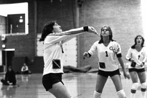 Black and white photo of three players, one with arms out to volley